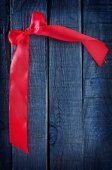 Red ribbon on wooden background — Stock Photo