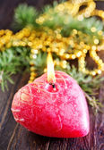 Red candle on the wooden table — Stok fotoğraf