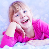 Smiling little girl lying on bed — Стоковое фото