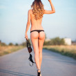 Sexy young woman going by the road and showing offensive gesture (middle finger). Rear view — Stock Photo #52826937
