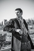 Portrait of handsome young man wearing jeans, coat and scarf — Foto de Stock