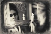 Beautiful goth girl holding candle in hand and looking into mirror. Grunge texture effect — Stock Photo
