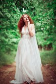 Beautiful redhead woman wearing white dress, in a forest — Stock Photo