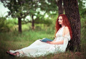 Cute red-haired woman sitting under tree and reading a book — Stock Photo