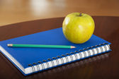 School supplies with apple on wooden table — Stock Photo