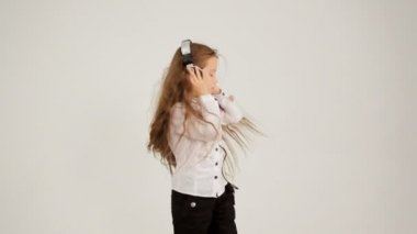 Little Girl Listening to Music With Headphones And Dancing. Video shot in opposite direction. — Stock Video