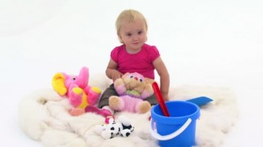 Baby Girl With Toys On White Cover — Stock Video