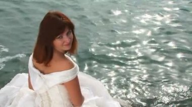 Young Pretty Woman In White Dress Sitting On Rock By Sea — Stock Video