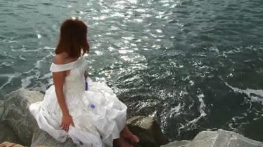 Pretty Young Woman In White Dress Sitting On Rock By Sea — Stock Video