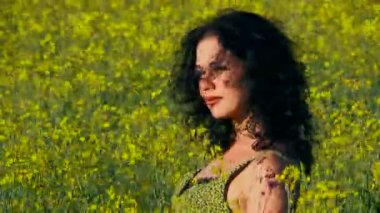 Curly woman is sitting in a field of Raps. — Vídeo de stock