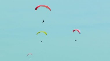 Four Paragliders Slowly Flying In The Blue Sky — Stock Video