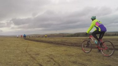 EDITORIAL. Young Bicycle Riders Moving In Field At Dull Day — Stock Video