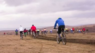 EDITORIAL. Group Of Young Bicycle Riders Moving In Field At Dull Day — Stock Video