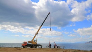 EDITORIAL. People With Crane-Machine Lifting Holiday Cruiser At Seashore — Stock Video