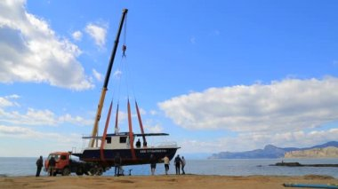 EDITORIAL. Workers Lifting Holiday Cruiser At Seashore With Crane-Machine — Stock Video