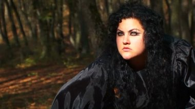 Dark Haired Woman In Black Staring Into The Distance In Autumn Forest — Stock Video