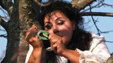 Crazy Dark-Haired Woman In Long White Nightie Putting On Mascara Sitting On Tree — Stock Video