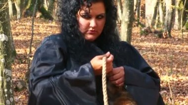 Woman In Black Tying Rope To A Fur Tail In Autumn Forest — Stock Video