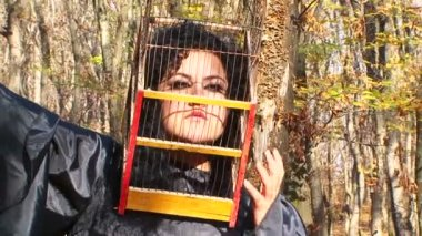 Woman In Black With Cage On Her Head In Autumn Forest — Vídeo de Stock