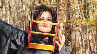 Frau In schwarz mit Käfig auf dem Kopf im Herbst Wald — Stockvideo