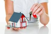 Real estate agent with house and key — Stock Photo