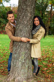Courting couple behind a tree — Stock Photo