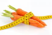 Fresh carrots with tape measure — Stock Photo