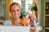 Woman with radiator and piggy bank — Stock Photo