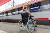 Woman sitting in a wheelchair on a train station — Stock Photo