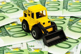 Excavator on euro banknotes — Stock Photo