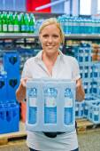 Woman buys bottled water at the grocery store — Stock Photo