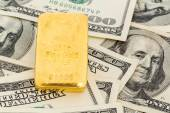 Gold bars on dollar bills — Stock Photo