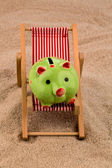 Beach chair with piggy bank — Stock Photo