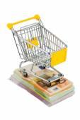Shopping cart on bills — Stock Photo