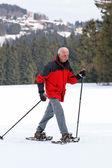 Senior snowshoeing in winter — Stock Photo