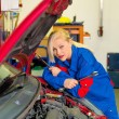 Woman as a mechanic in auto repair shop — Stock Photo #67137611