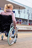 Woman sitting in a wheelchair at a train station — Stock Photo