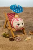 Beach chair with piggy bank and euro — Stock Photo