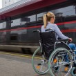 Woman sitting in a wheelchair at a train station — Stock Photo #73484779