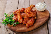 Battered chicken wings in red spicy sauce — Stock Photo