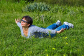 Woman lying on a green grass  — Stock Photo