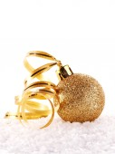 New Year's golden ball on snow with a tape. — Stock Photo