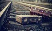 Two old fashioned a suitcases on railroad tracks — Stock Photo