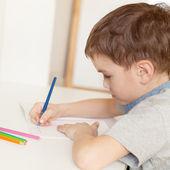 Serious pensive pupil sits at desk — Stock fotografie