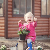 Cute baby girl in pink dress puts flowers — Stock Photo