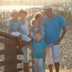 Happy beautiful family standing on bridge — Stock Photo #78698772