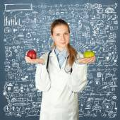 Female doctor with two apples — Stock Photo