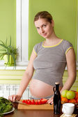 Pregnant woman cooking healthy food — Stock Photo