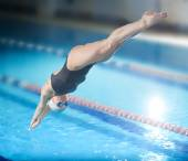 Female swimmer jumping into swimming pool. — Foto de Stock