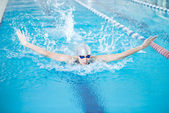 Girl swimming in butterfly stroke style — Stockfoto